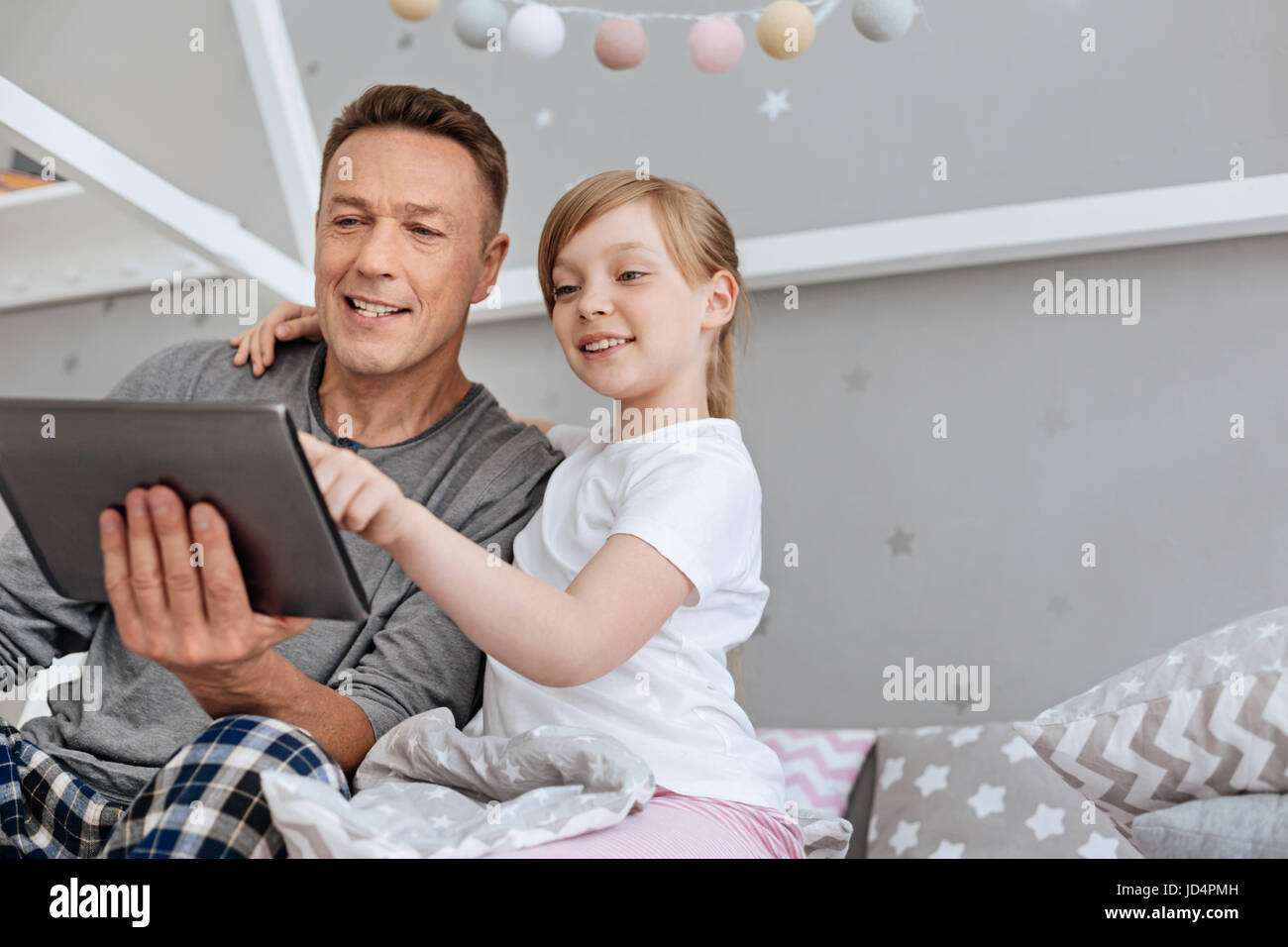 Cute engaged family watching something on tablet - Stock Image