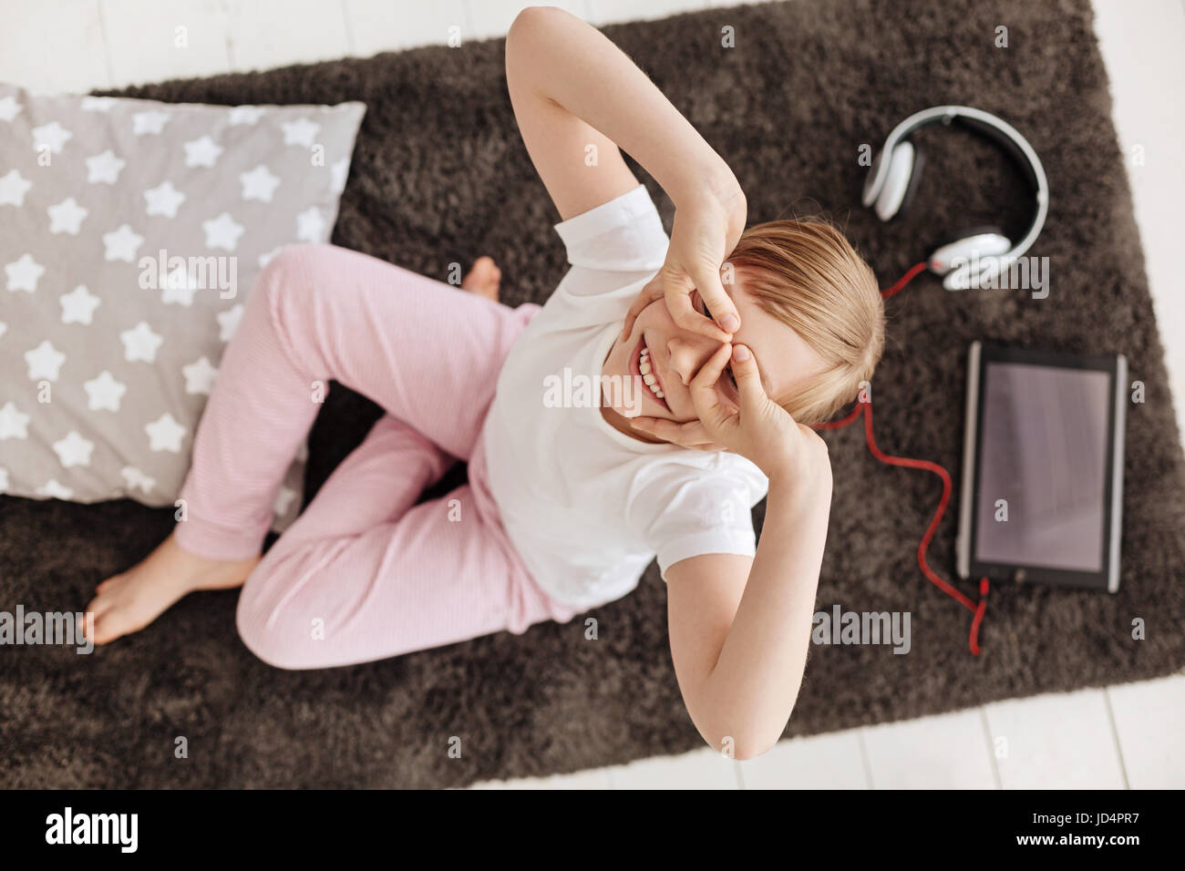 Hilarious cute girl goofing around in her room - Stock Image