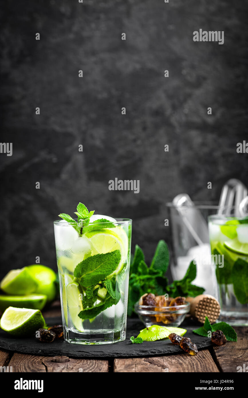 Refreshing mint cocktail mojito with rum and lime, cold drink or beverage with ice on black background - Stock Image