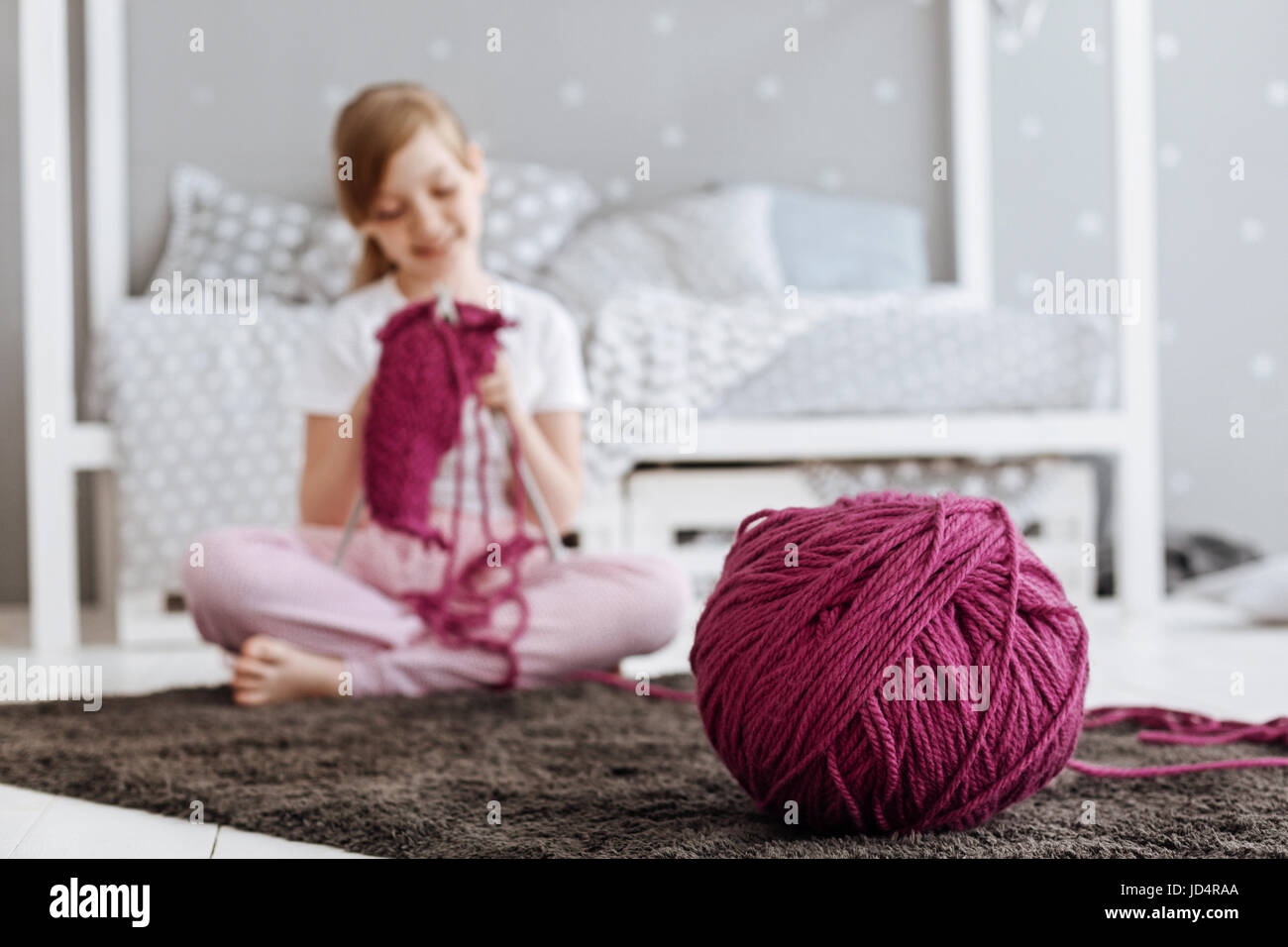 Cute diligent little girl knitting something - Stock Image
