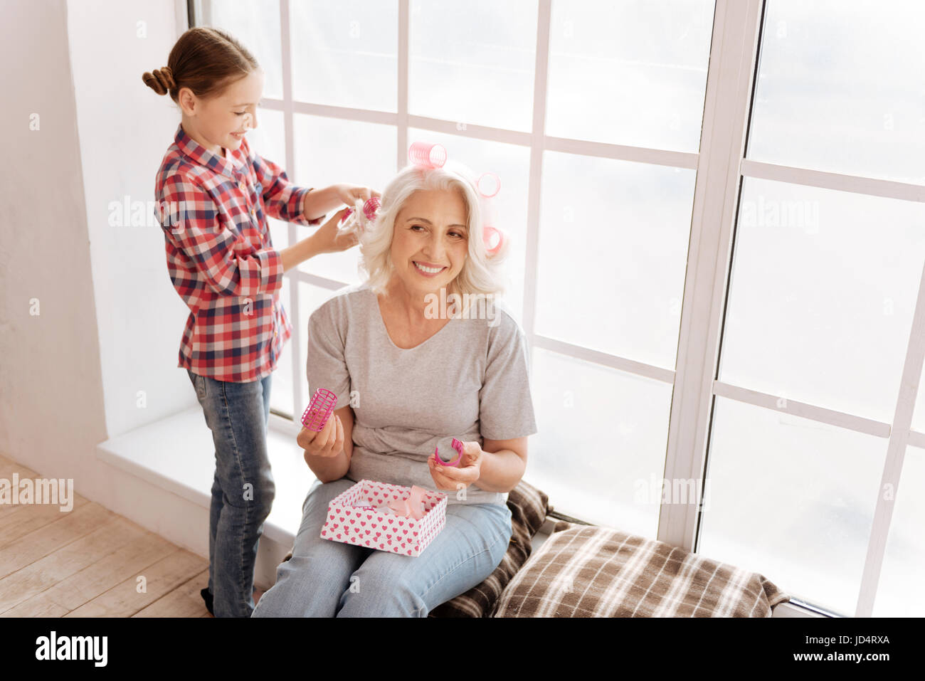 Positive cheerful girl using hair rollers - Stock Image