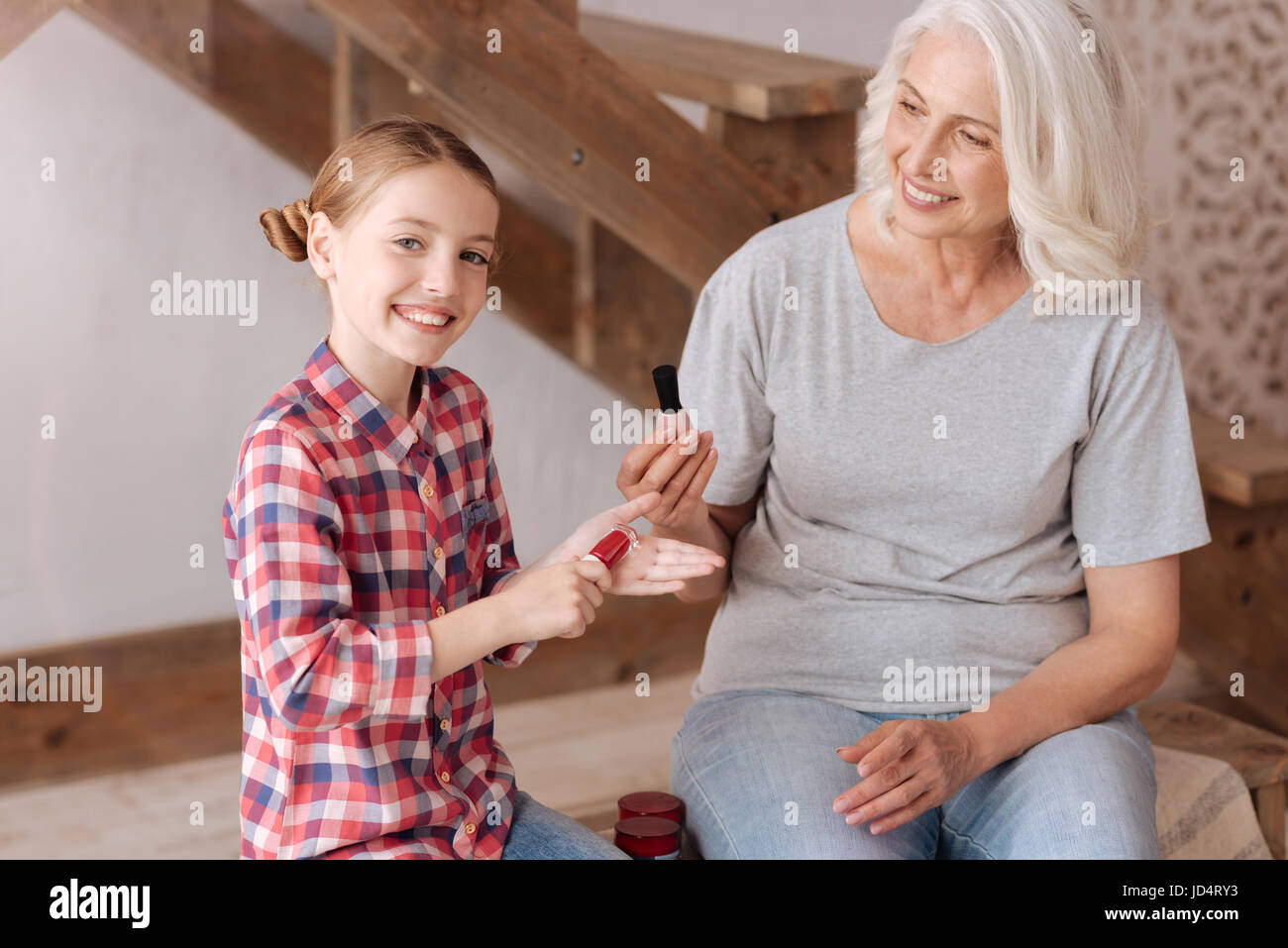 Positive cheerful girl holding a nail varnish bottle - Stock Image