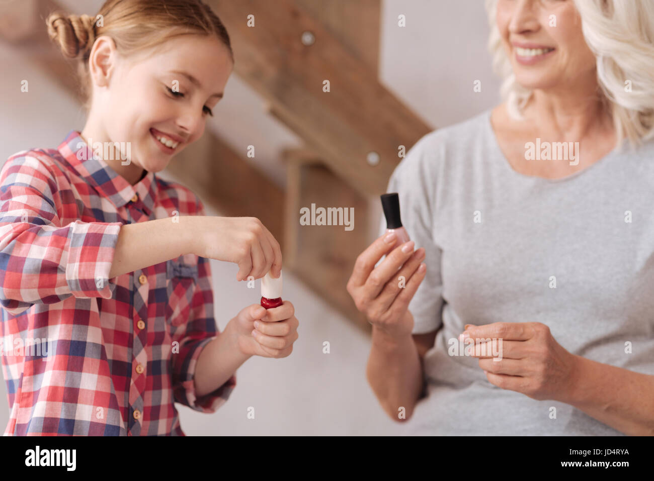 Happy pretty girl opening a nail varnish - Stock Image