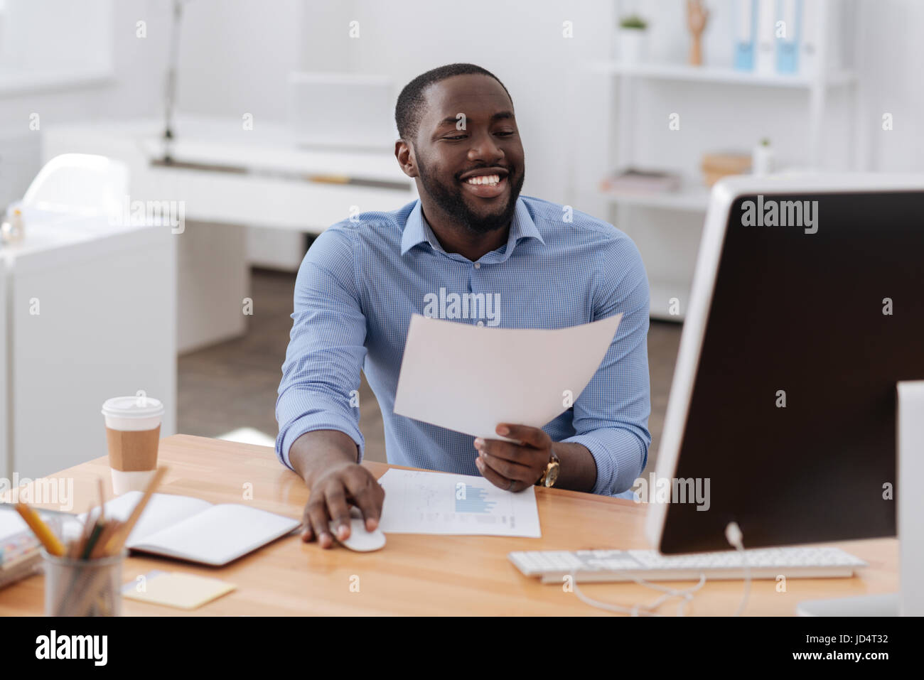 Positive happy man holding a computer mouse - Stock Image