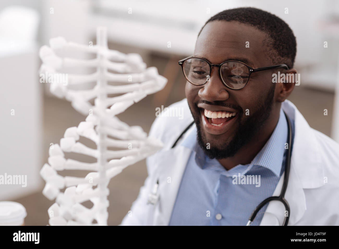 Smart modern scientist looking at the gene model - Stock Image