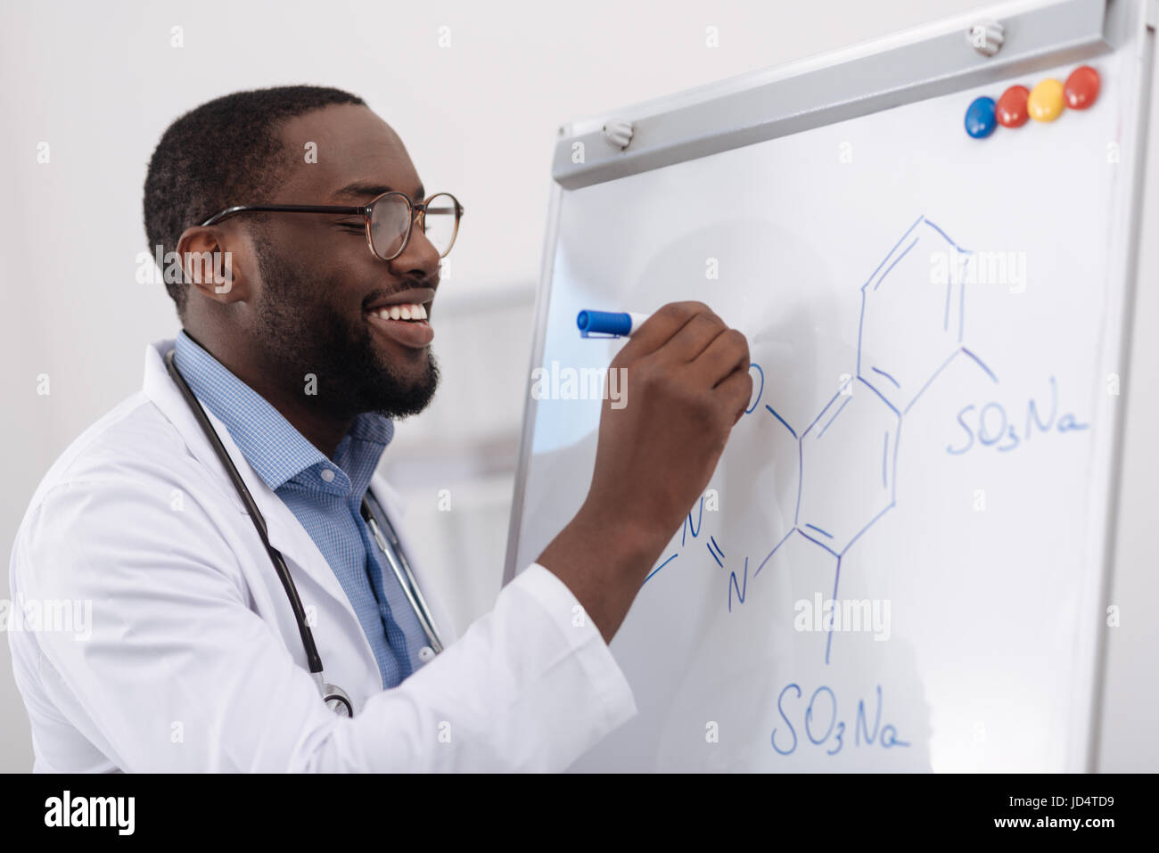 Handsome positive chemist writing a formula - Stock Image