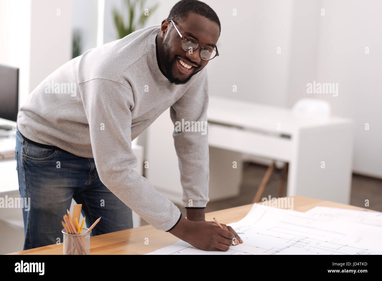 Joyful positive man doing a draft - Stock Image