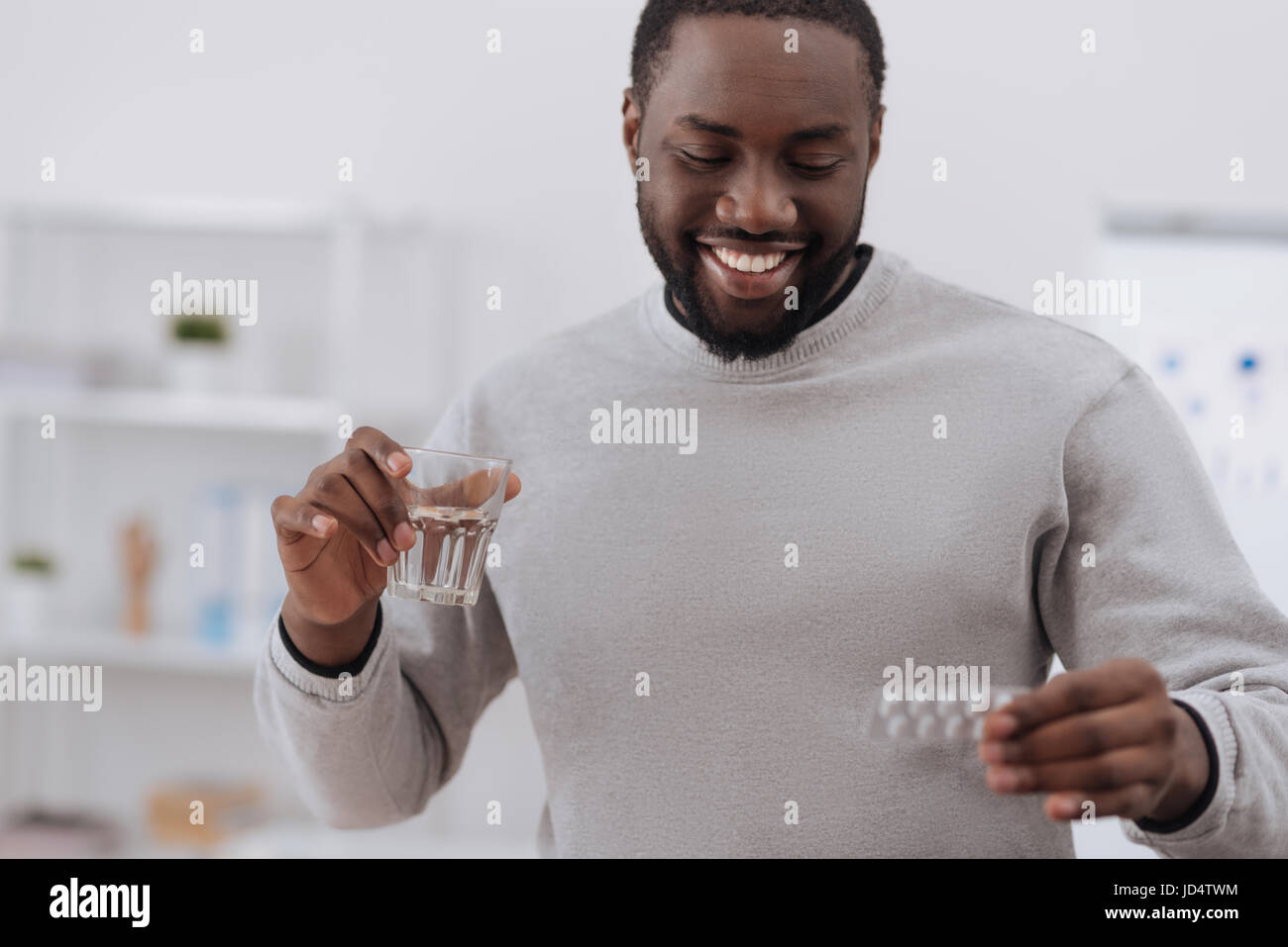 Joyful nice man looking at the pills - Stock Image