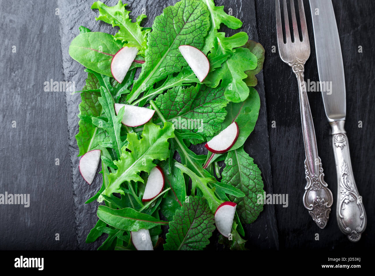 Mixed salad leaves with radish on black slate plate. Top view - Stock Image