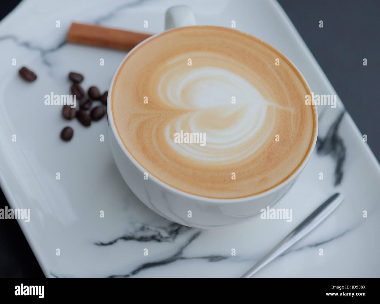 Latte art coffee. Heart shape latter art in white cup - Stock Image