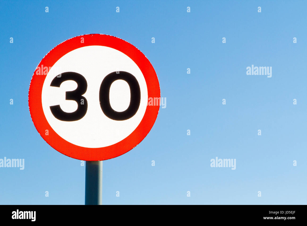 Left sided thirty miles per hour speed limit sign against blue sky with copyspace - Stock Image