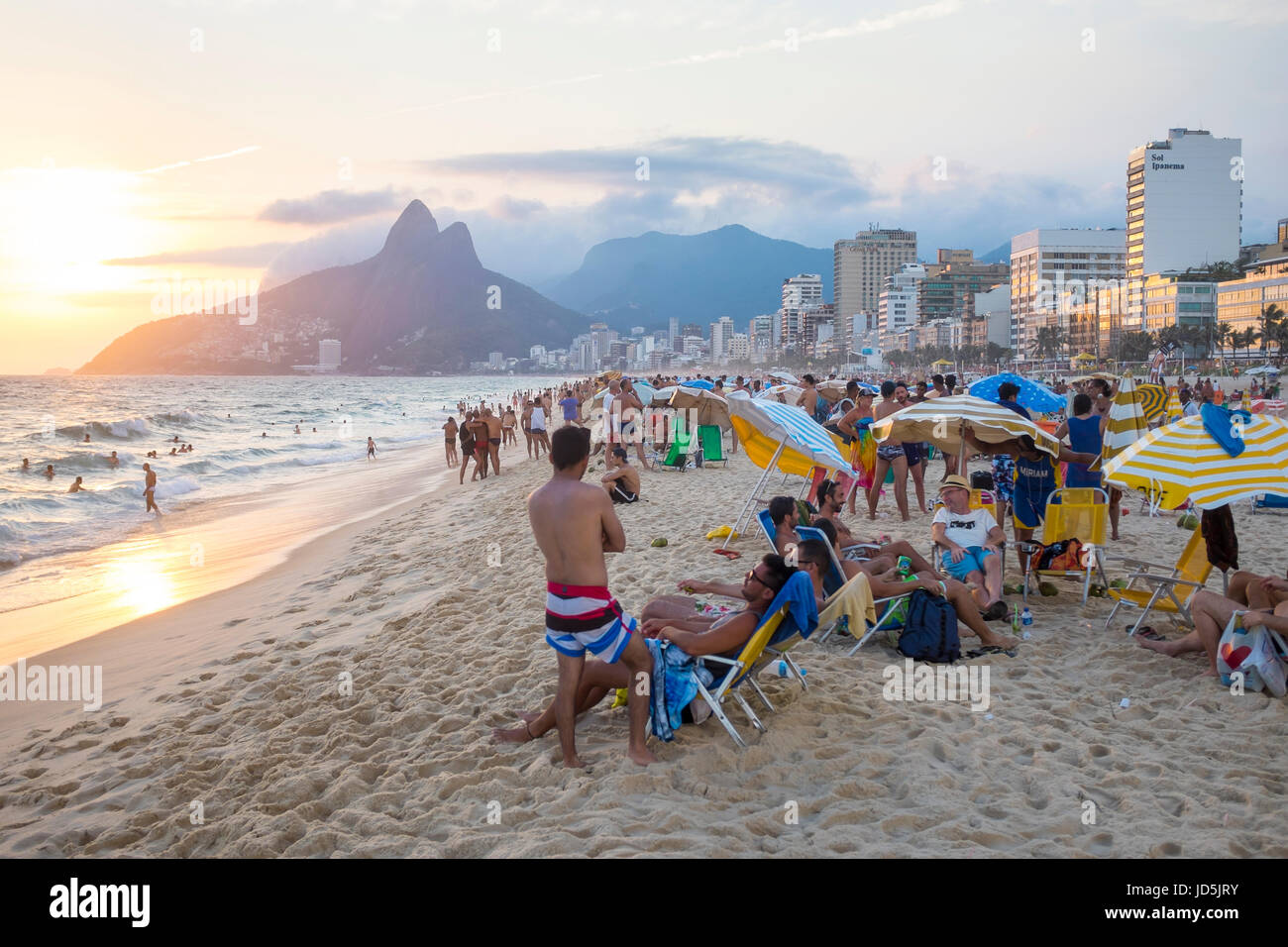 RIO DE JANEIRO - JANUARY 27, 2017: Beachgoers on Ipanema Beach sit back to take in the sunset behind Two Brothers - Stock Image