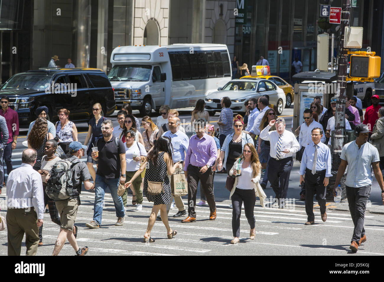 Crowds of pedestrians cross 5th Avenue along 42nd Street in midtown Manhattan. - Stock Image