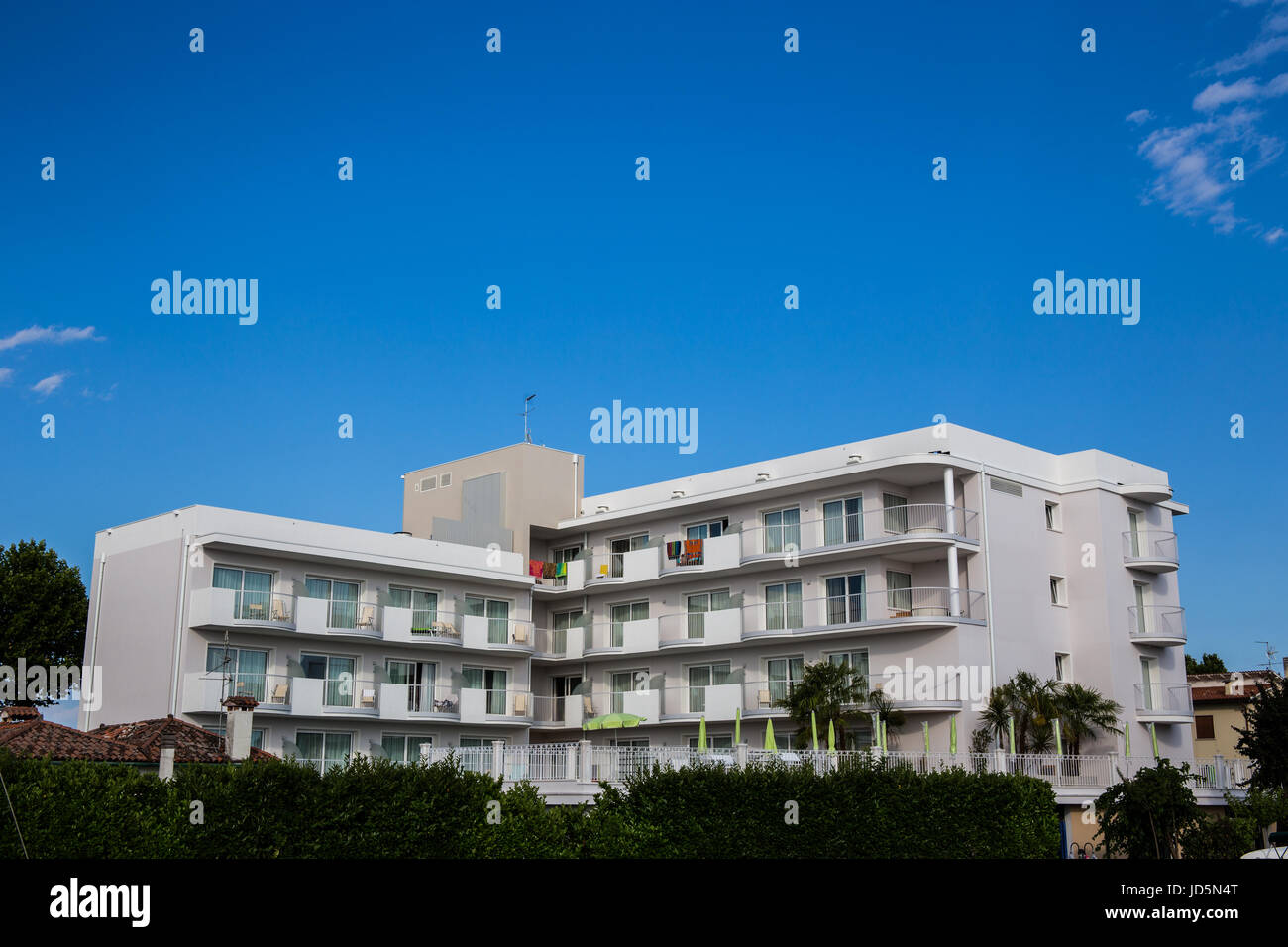 Newly built apartment block with beautiful blue sky in the background. Caorle - Italy - Stock Image