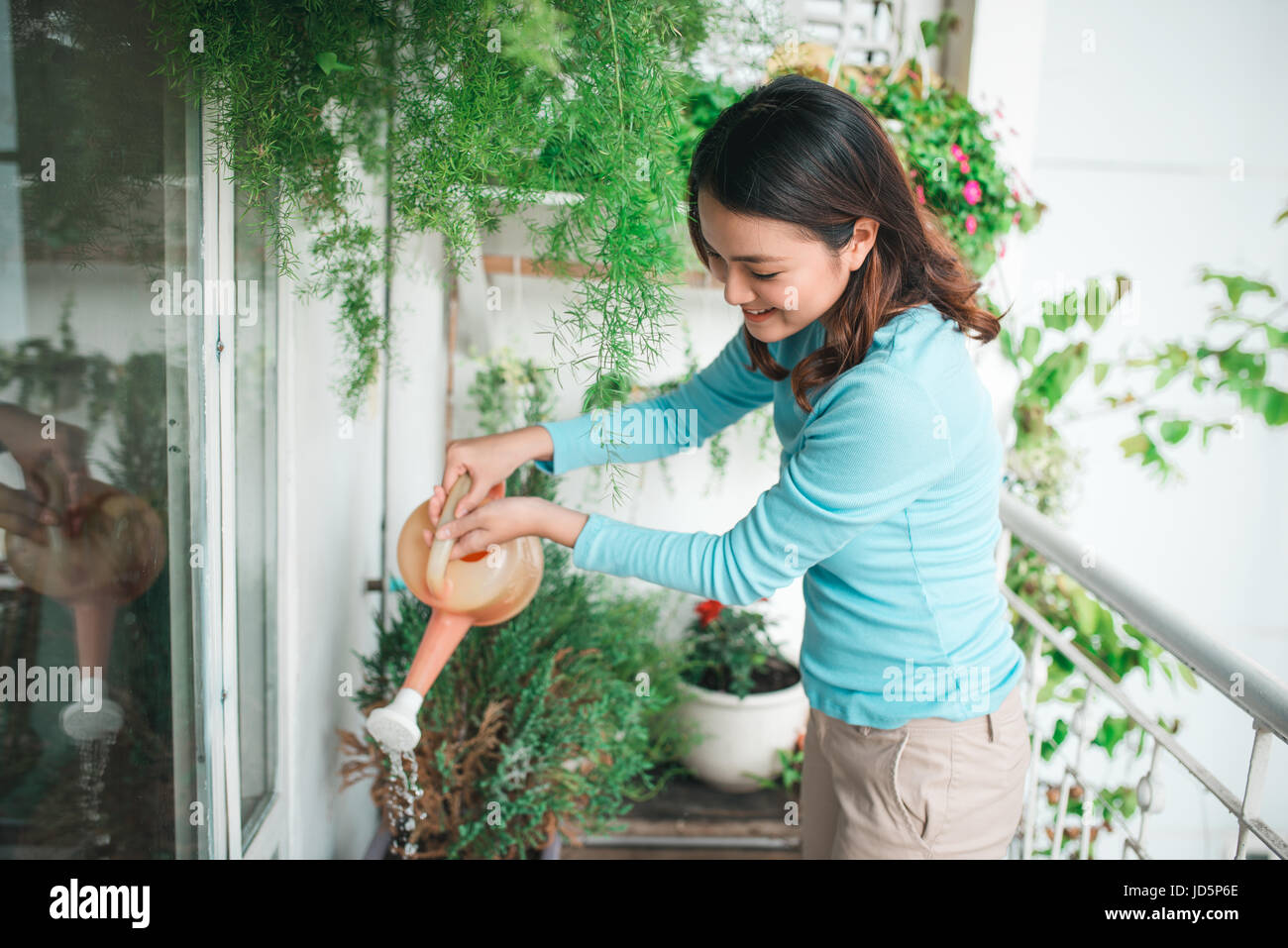 Woman wtering plant in container on balcony garden - Stock Image