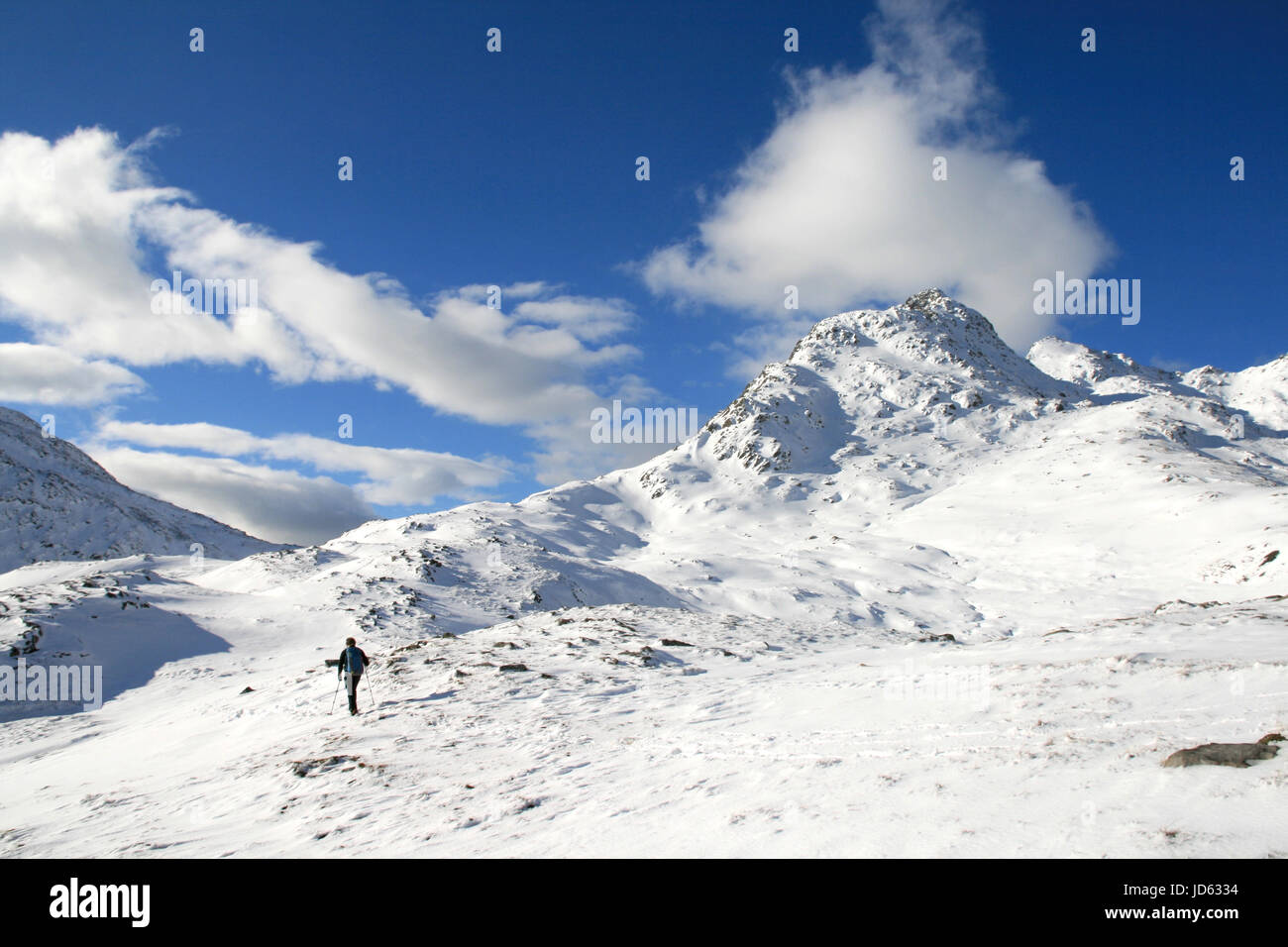 Scottish winter mountaineer walking towards the start of a snow covered Forcan Ridge in Glen Shiel. - Stock Image
