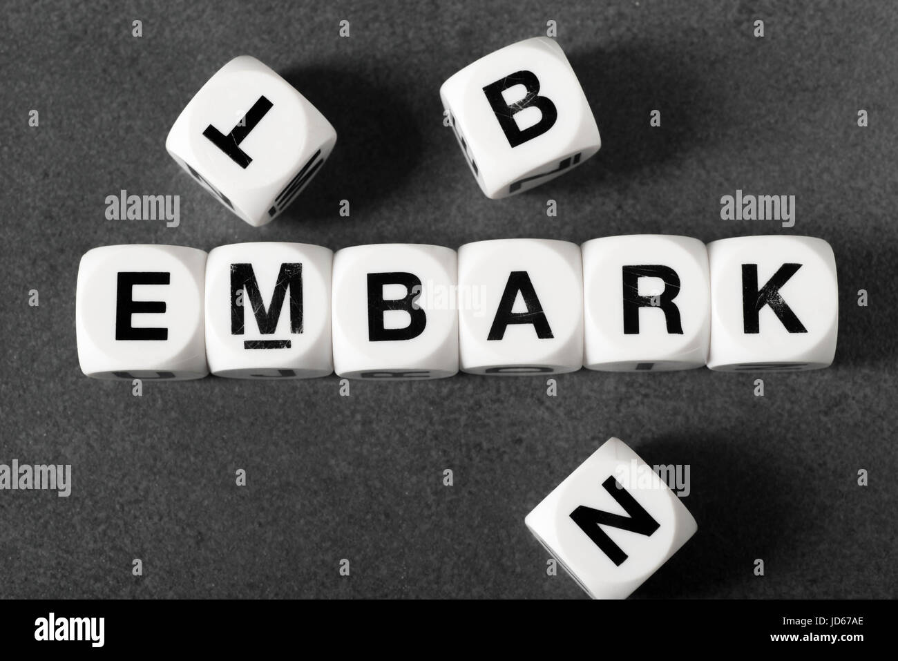 word embark on white toy cubes - Stock Image