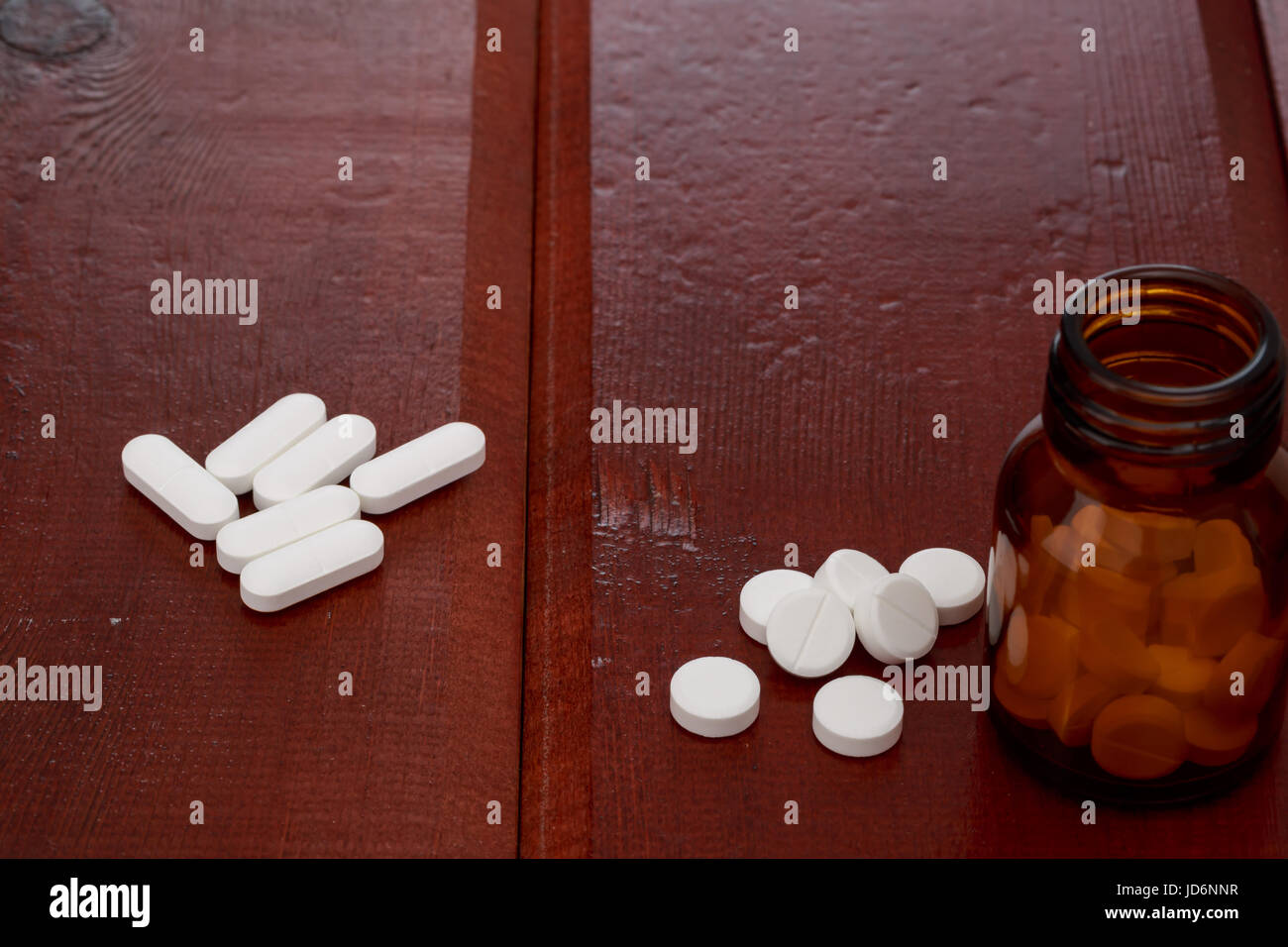 Brown pills bottles and heap of white pills on wooden table Stock Photo