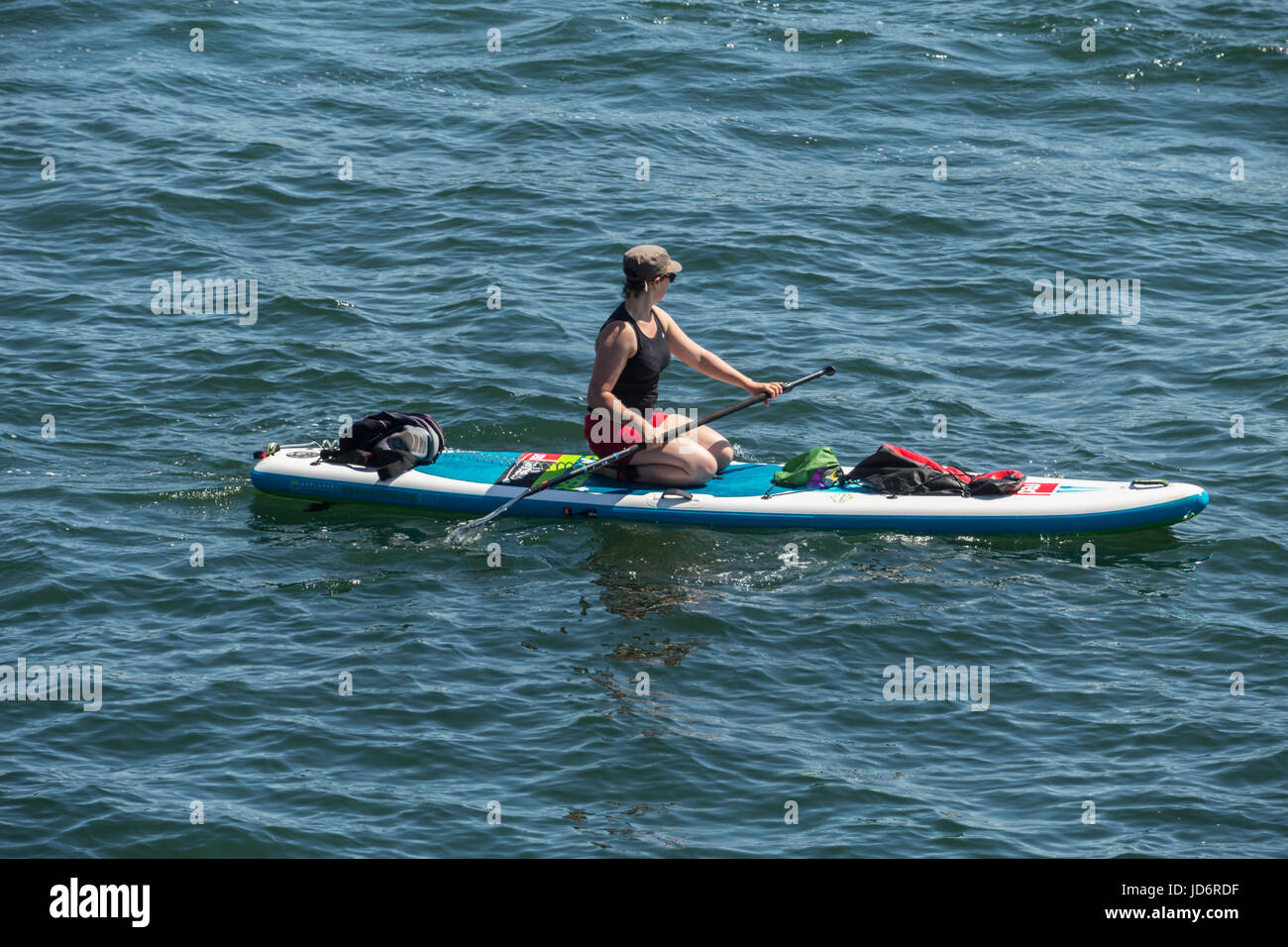 A young woman paddle boarding in Plymouth Sound on a hot clear day. - Stock Image