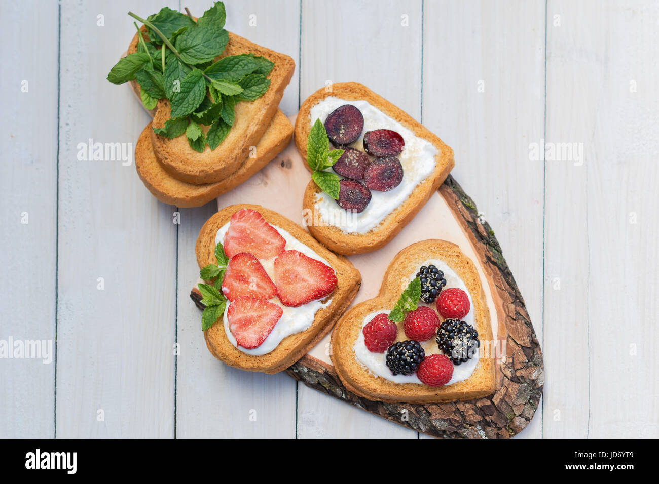 Heart shaped biscuits spread with quark, strawberries, blackberries, raspberries, cherries and a twig of mint presented - Stock Image