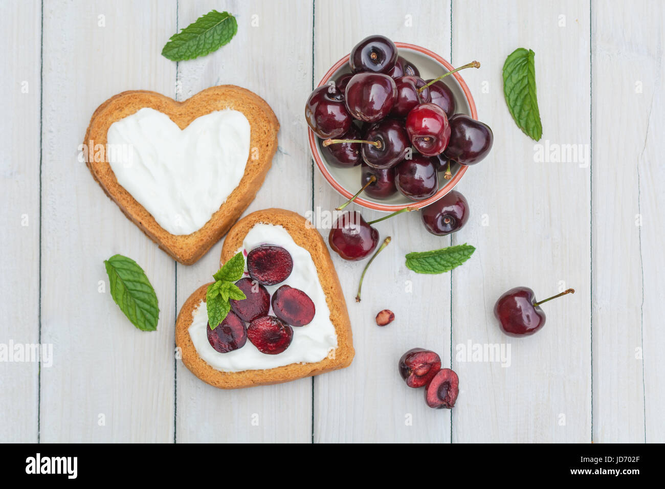 Bowl filled with cherries and heart shaped biscuits spread with quark,  cherries and a twig of mint Stock Photo