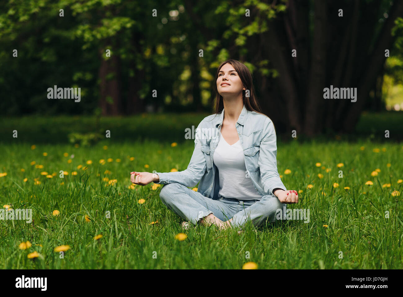Beautiful young girl in casual clothes meditating in spring park - Stock Image