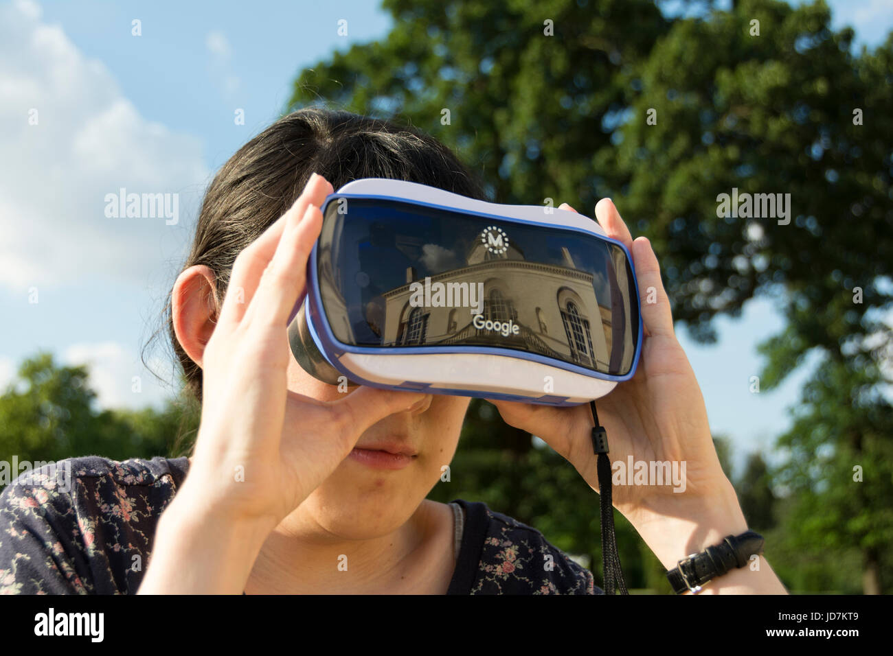 A young woman experimenting with a Google Expeditions headset - Stock Image