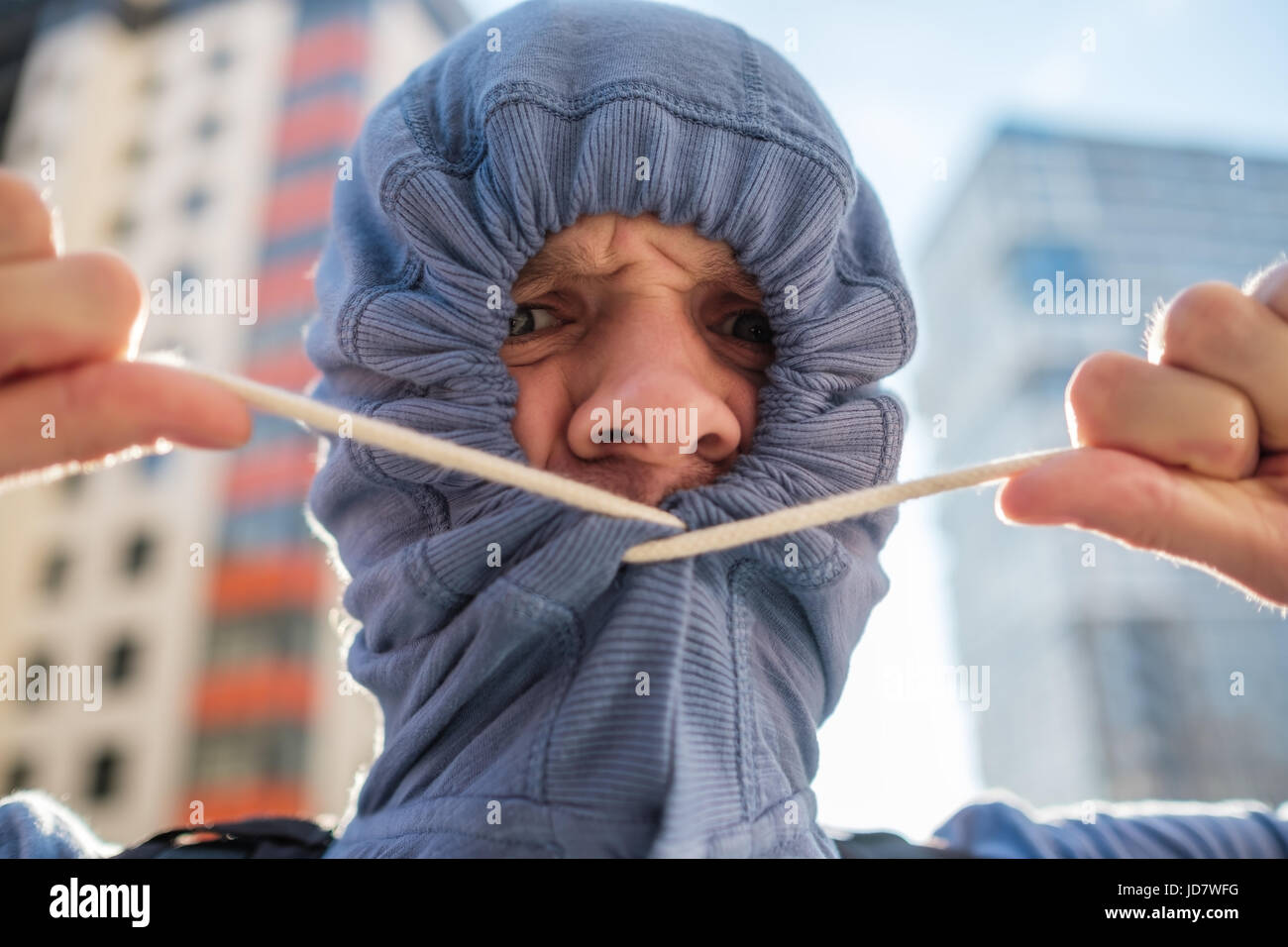 Caucasianyoung man hiding unshaven face with hood. Secrecy and mystery. Sociopathy and fear of going out. - Stock Image