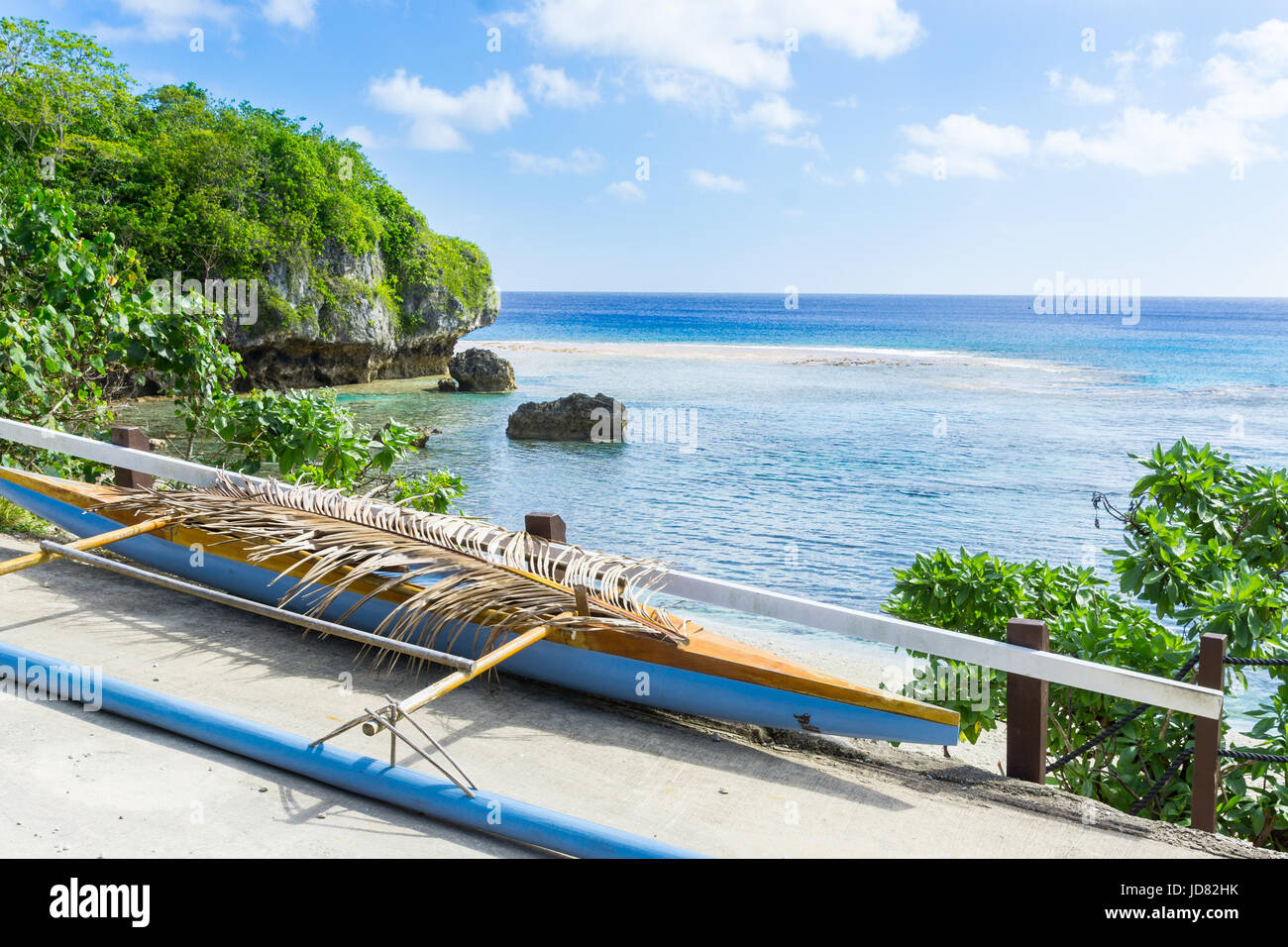 Out-rigger canoe under palm frond to shield some rainwater from boat on ledge overlooking scenic coastline and vast Pacific Island, Niue. Stock Photo