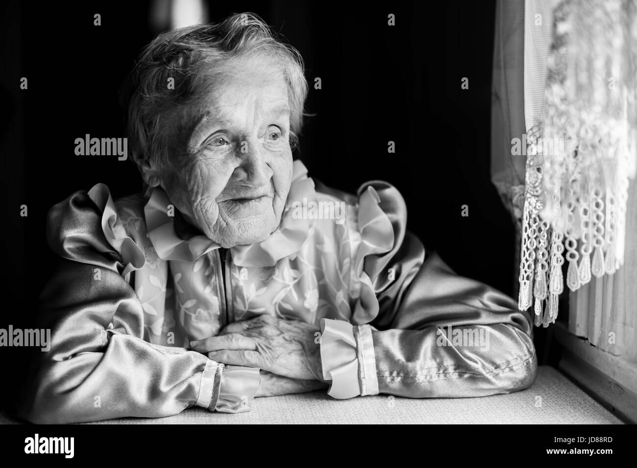 An elderly woman sitting near the window. Slavic Grandmother, a black and white portrait. - Stock Image
