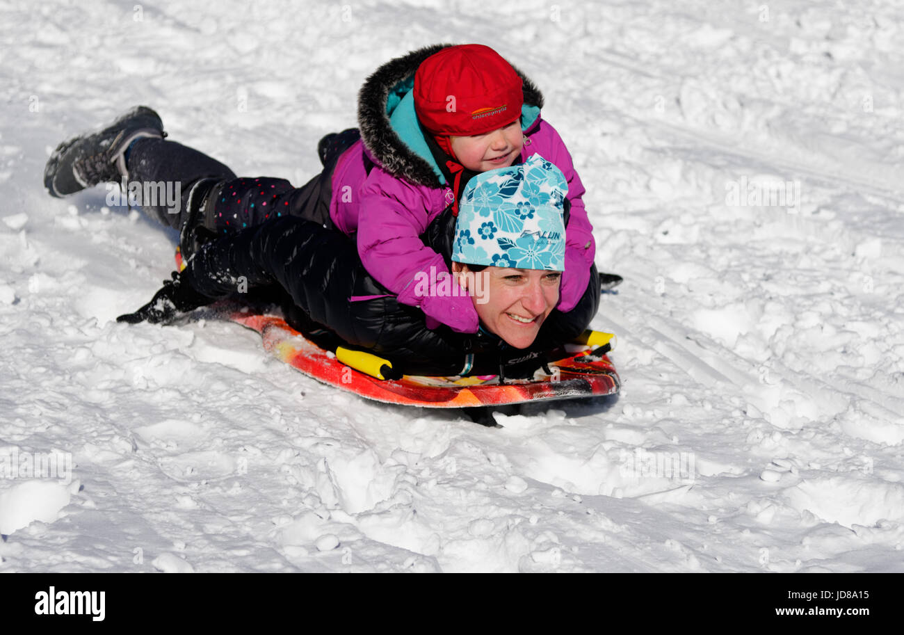 A young child riding on the back of an adult on a sledge - Stock Image