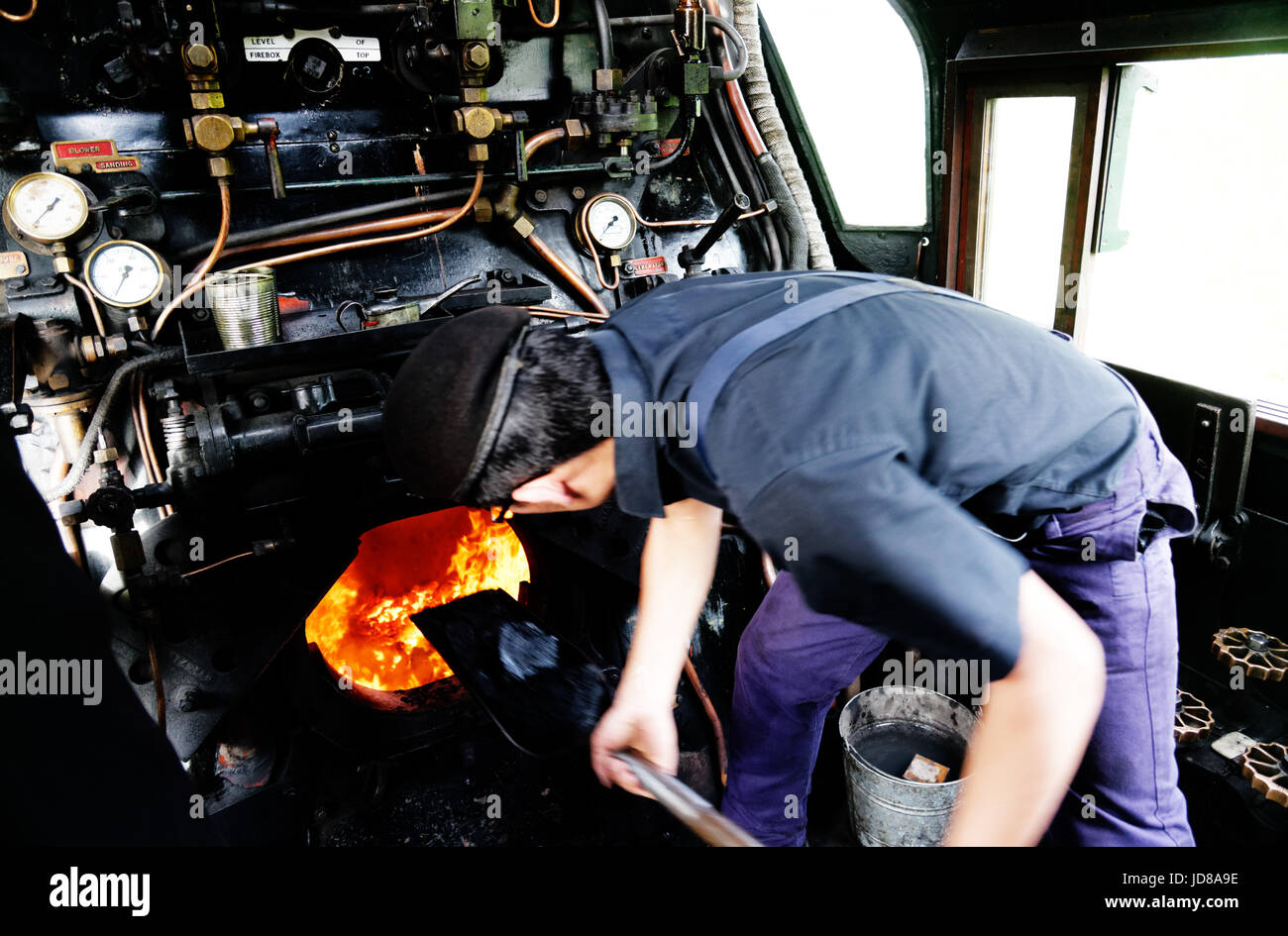A stoker shovelling coal into the firebox on the Battle of Britain class locomotive Manston 34070 - Stock Image