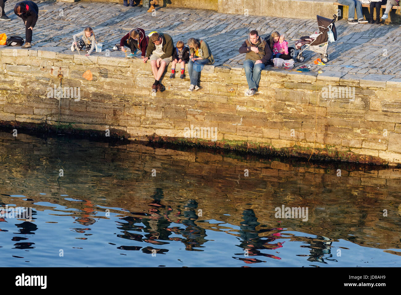 People catching crabs off the pier at Swanage in Dorset - Stock Image