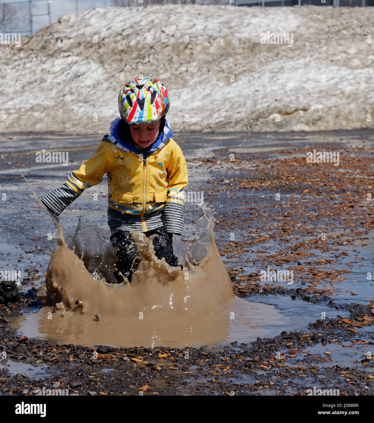 A young boy (5 yrs old) leaping into a muddy puddle. - Stock Image