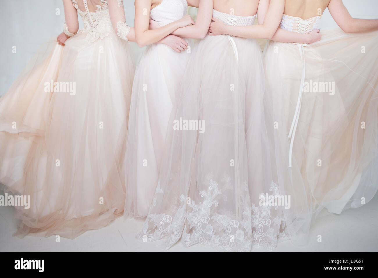 8629b7845767 Four beautiful bridesmaid dresses in pastel colors are in each other's  arms. Back, close-up lace skirts