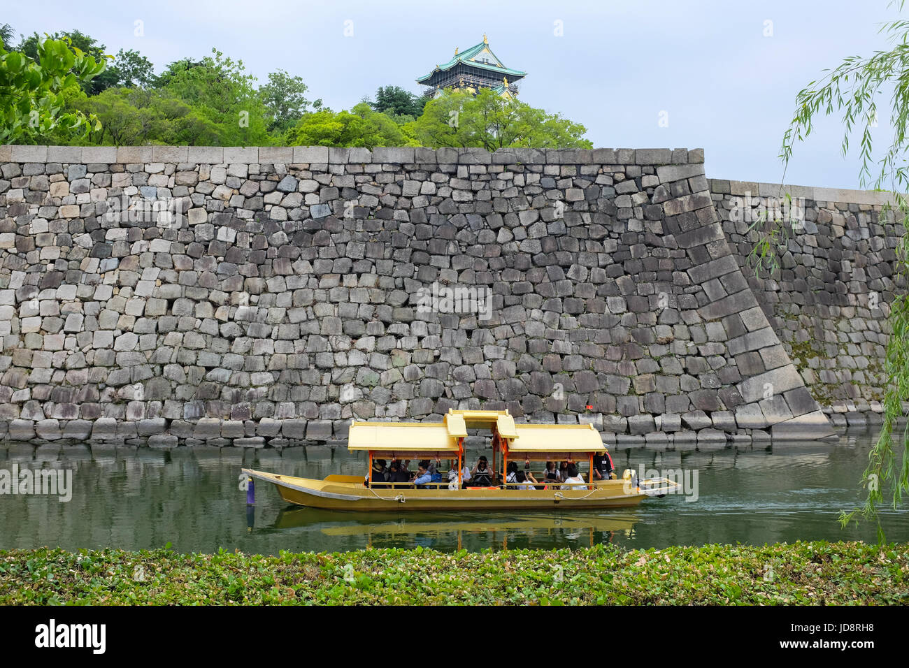 A boat taking tourists on a trip on the moat of Osaka Caslte in the city of Osaka, Japan. - Stock Image