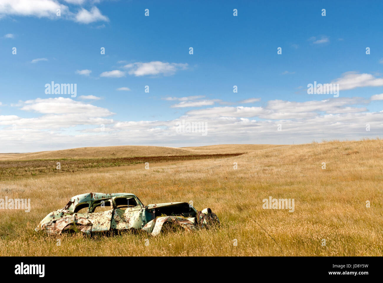 vintage car abandoned in prairie field - Stock Image
