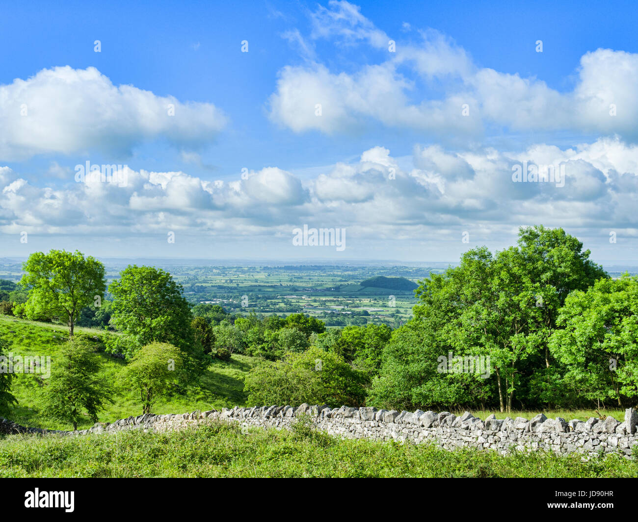 A dry stone wall at the top of the Cheddar Gorge, and a view of the Somerset Levels, from the Gorge Walk, Somerset, - Stock Image