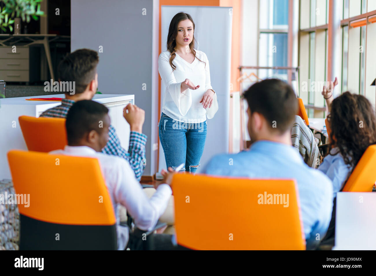 Pretty young business woman giving a presentation in conference or meeting setting. - Stock Image