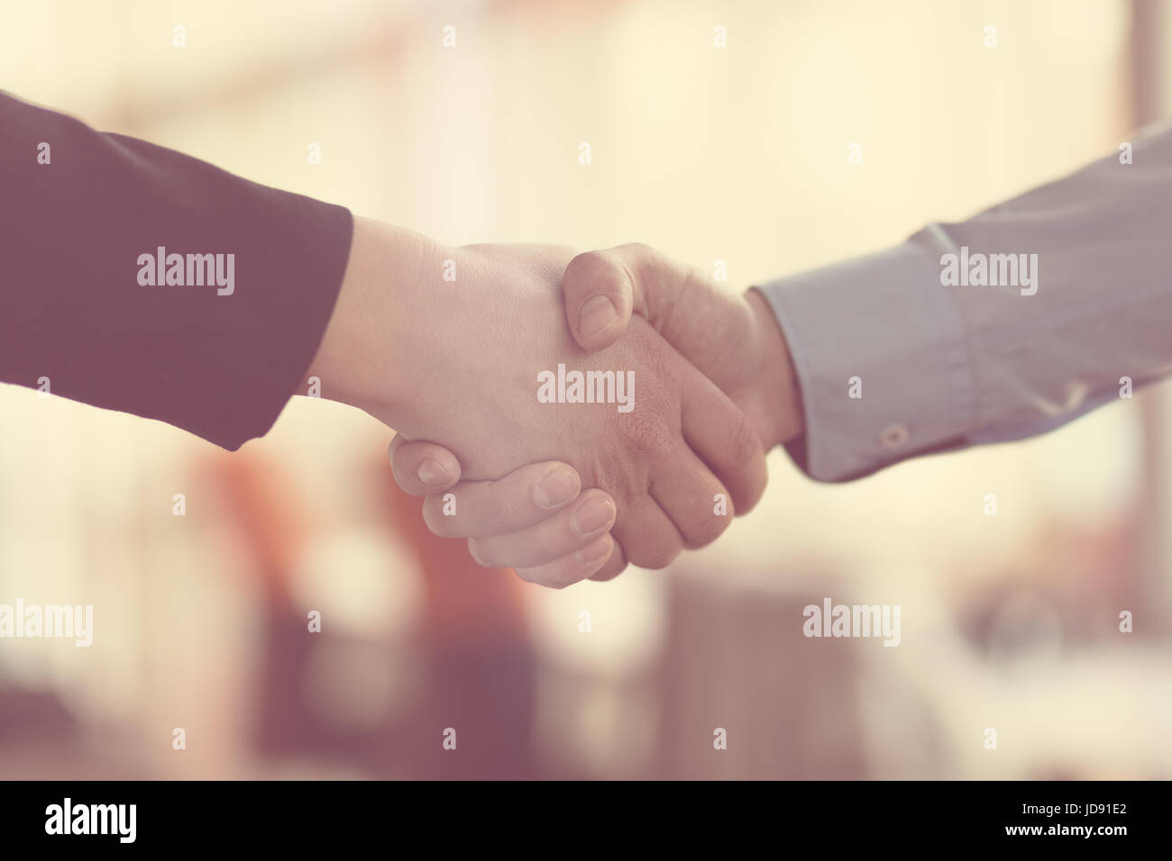 People at work: man and woman hand shaking at a meeting - Stock Image