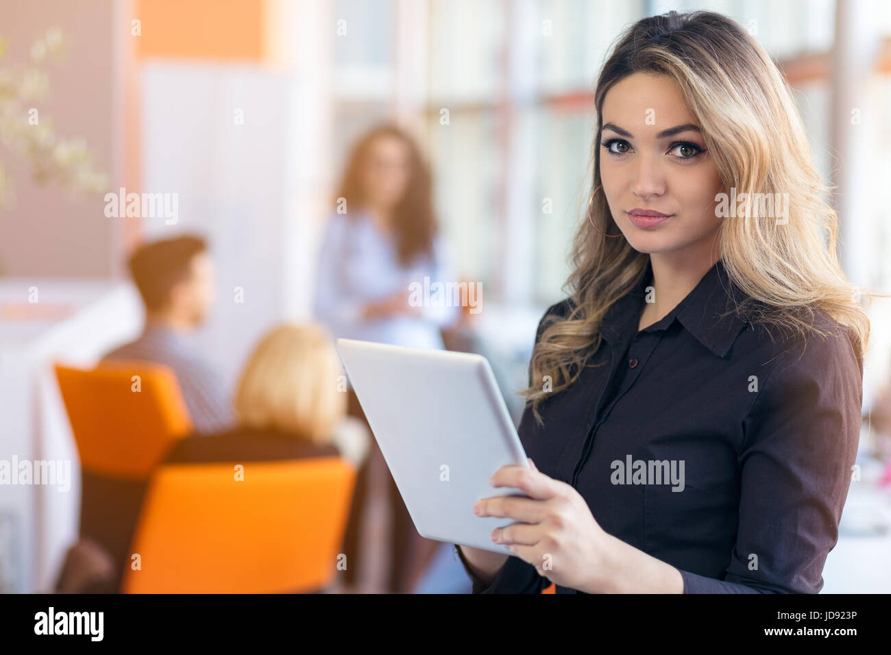 portrait of young business woman at modern startup office interior, team in meeting in background - Stock Image