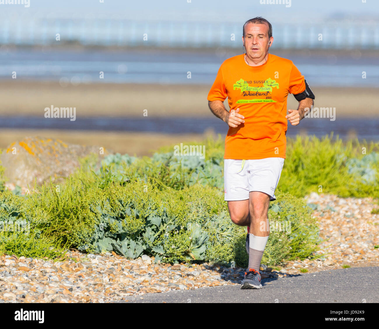 Man jogging along the seafront road in the early morning in Summer on a hot day. - Stock Image