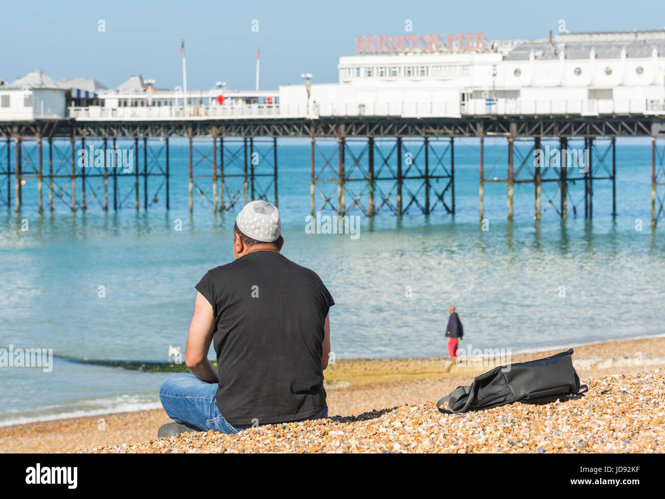 Man wearing a Muslim Taqiyah prayer cap, sitting along on Brighton Beach near Brighton Pier on a sunny day. - Stock Image