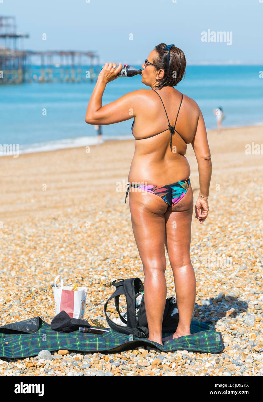 Summer concept. Summer drink. Very tanned woman in bikini having a drink on the beach on a hot Summers day in Brighton, - Stock Image