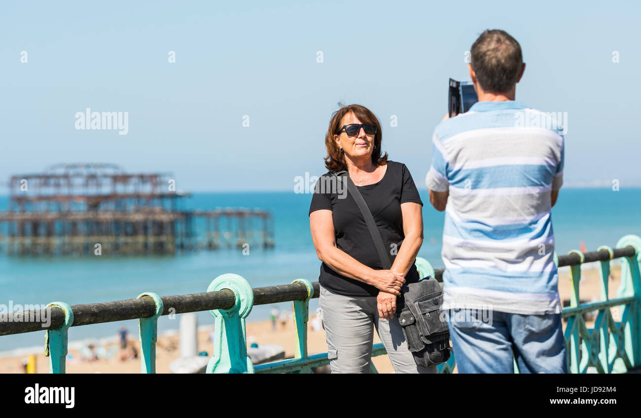 Family snapshots. A couple on a seaside promenade taking photos of each other for their summer holiday memories. - Stock Image