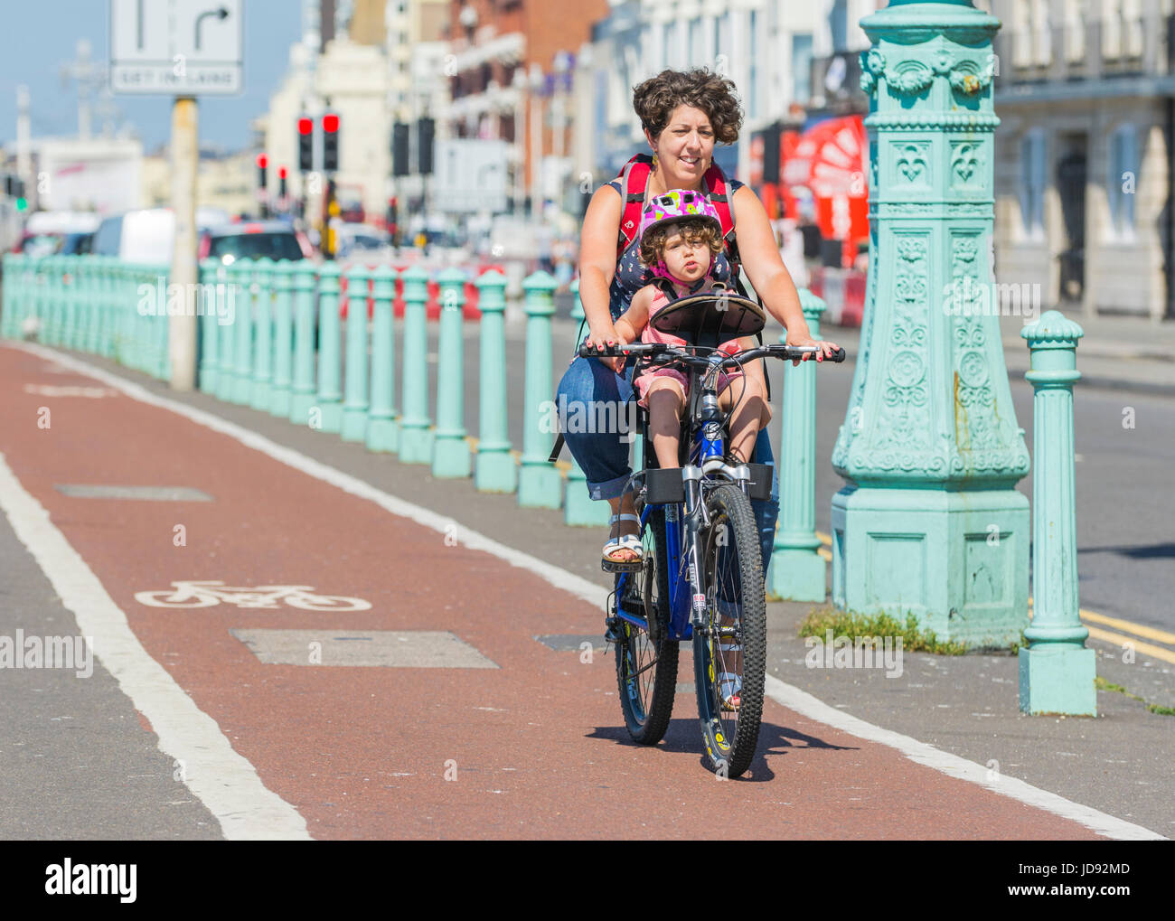 Cycling with a child. Woman cycling along a cycle path carrying a child. - Stock Image