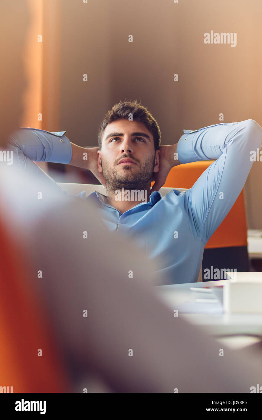 caucasian business person sitting in office thinking daydreaming hands behind head. - Stock Image