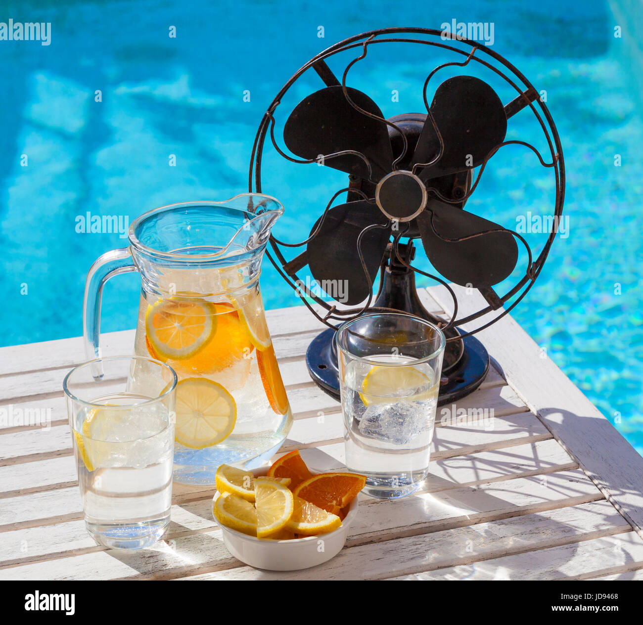 Hot summer day during a heat wave. A jar of refreshing water and a vintage fan at the pool. - Stock Image