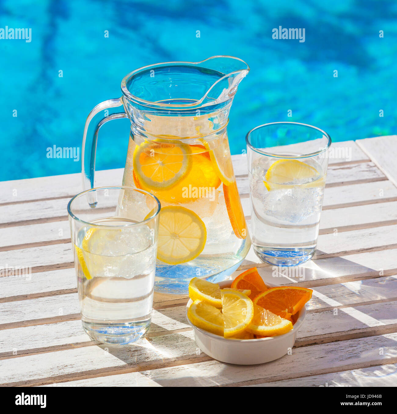 A jar and two glasses of refeshing ice water for hydration in hot weather. - Stock Image