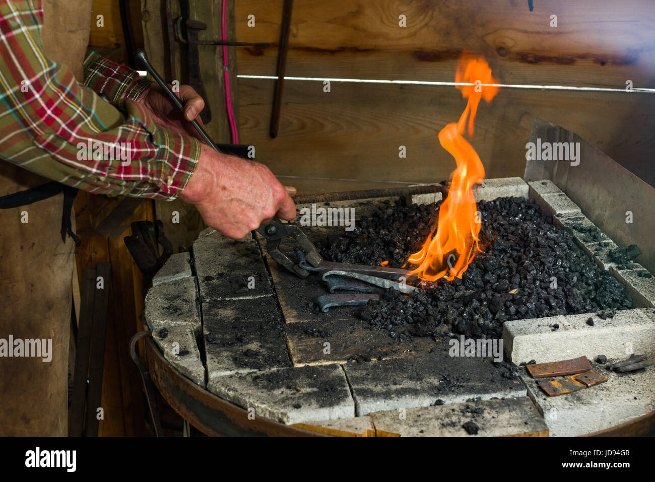 Blacksmith Heating Steel In Charcoal Forge In Workshop - Stock Image